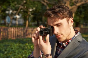 Man shooting with the Sony RX100 III through the viewfinder